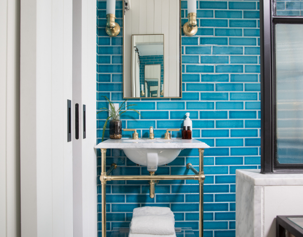 white pedestal sink with blue subway tile wall and mirror